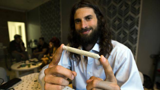 Chris Enns of The Farm Assists Cannabis Resource Centre on Gottingen Street holds up a joint on July 16. (TED PRITCHARD/ Staff/ File)
